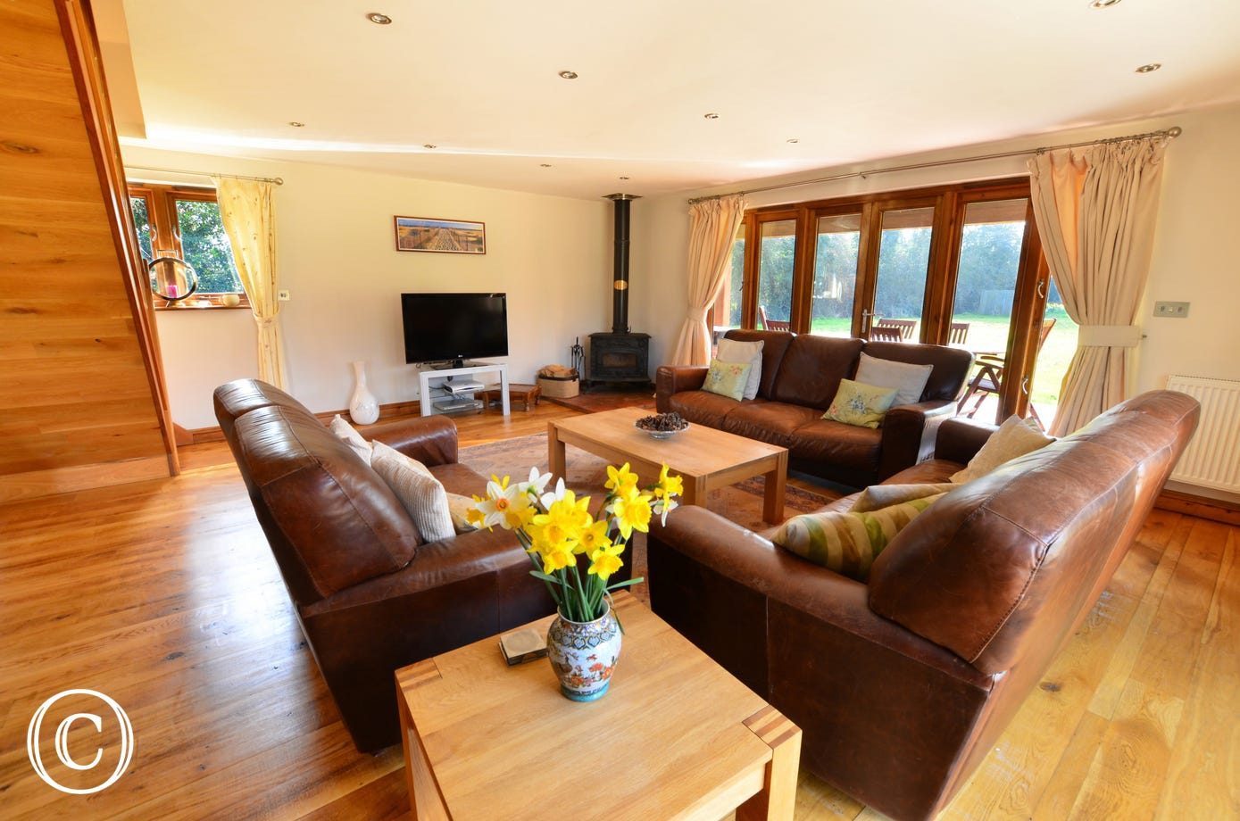 The sitting room is large and spacious with a polished wood floor