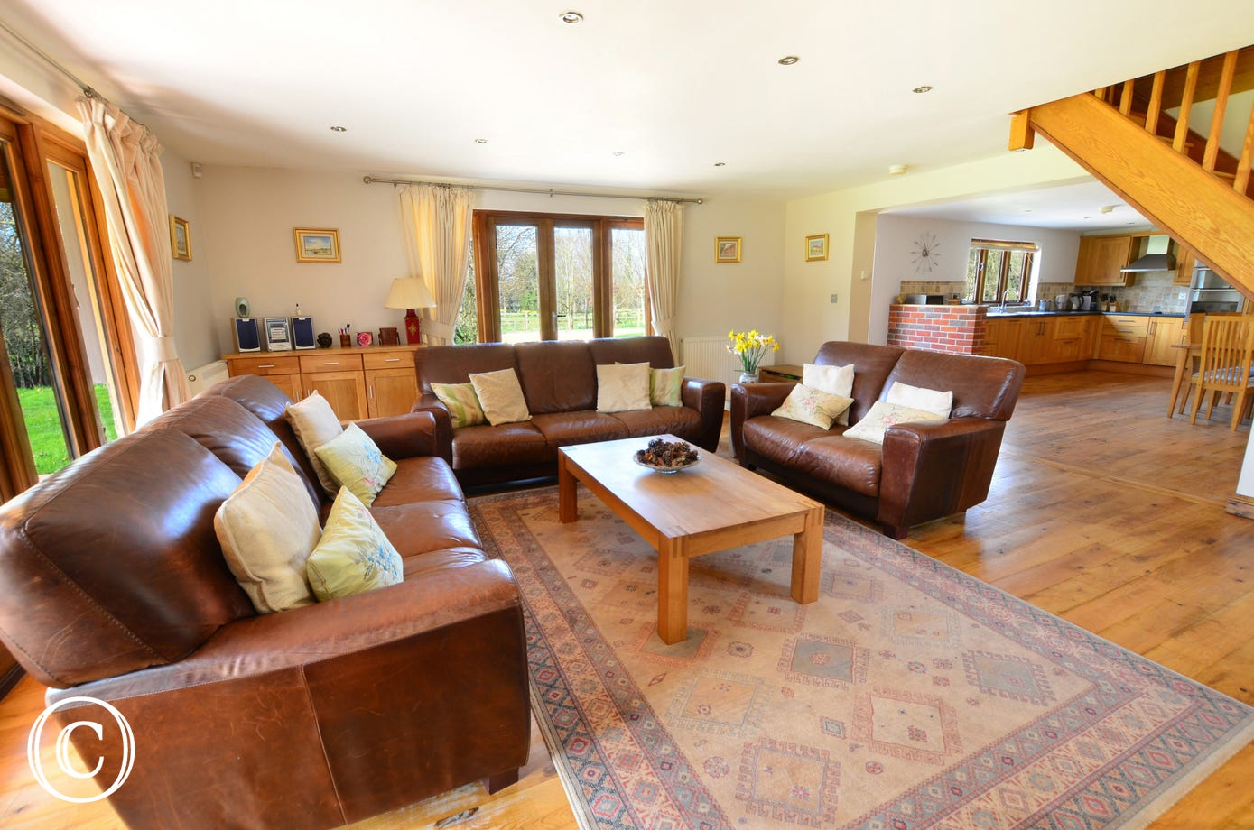 Light and airy with comfortable leather sofas in the sitting area and french doors to the garden