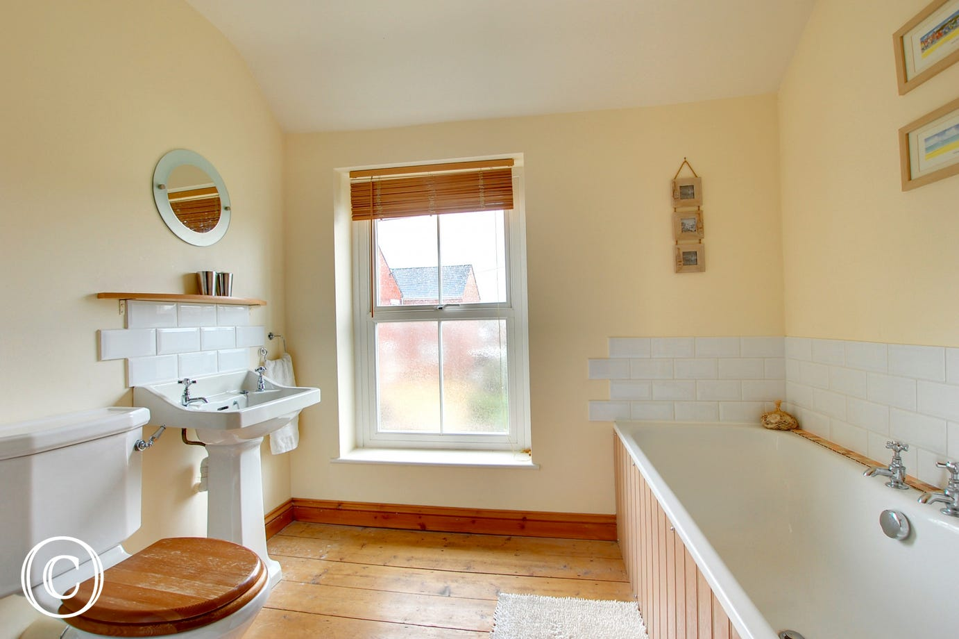 The bathroom is large and traditional with a window looking to the front of the property and wooden floor