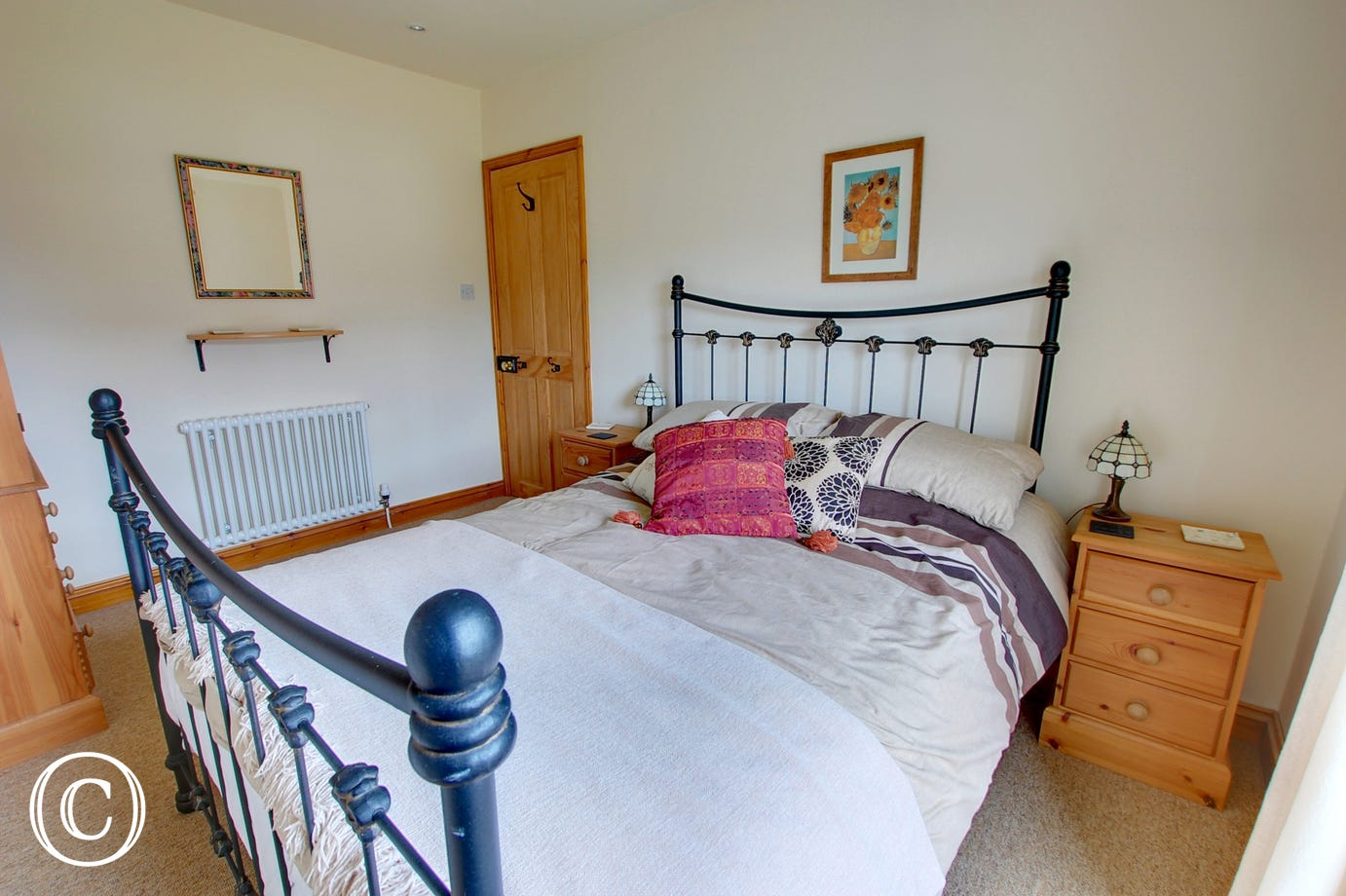 The double room has a double bed with an attractive iron bedstead, the room is light and airy and the window looks out over the front garden