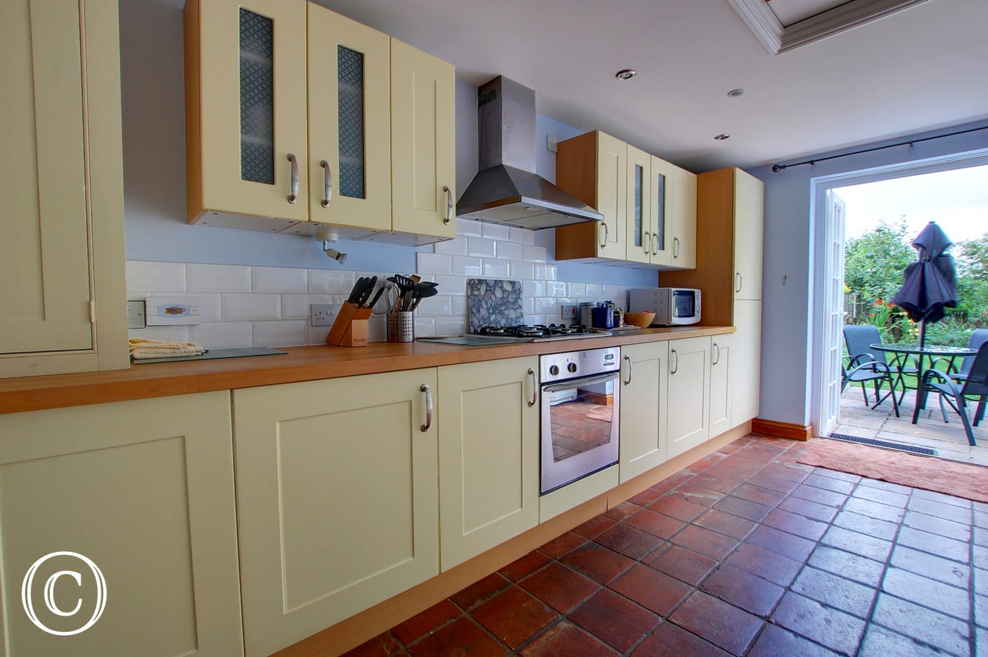 The spacious kitchen opens off the dining area and has cream cupboards and a ceramic tiled floor