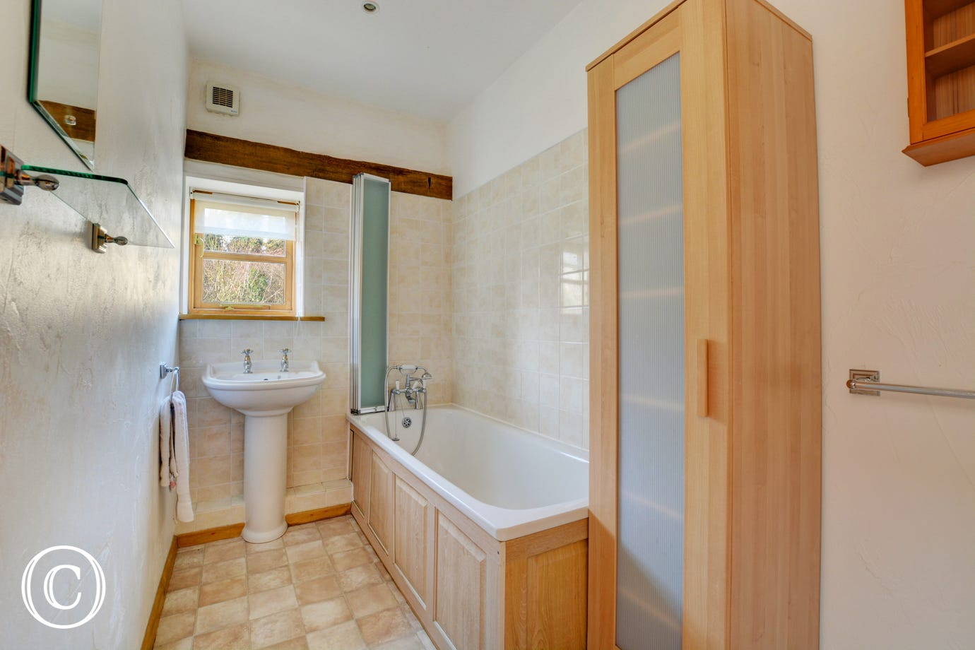 The bathroom is on the first floor and has a white suite and pale wood cupboards