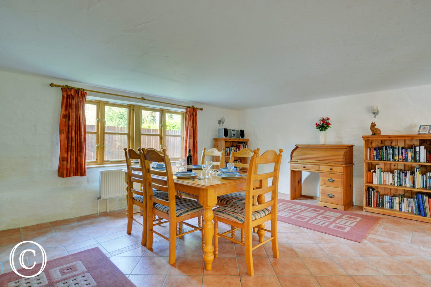 A pine table and six chairs stand in the centre of the large dining area, perfect for family meals