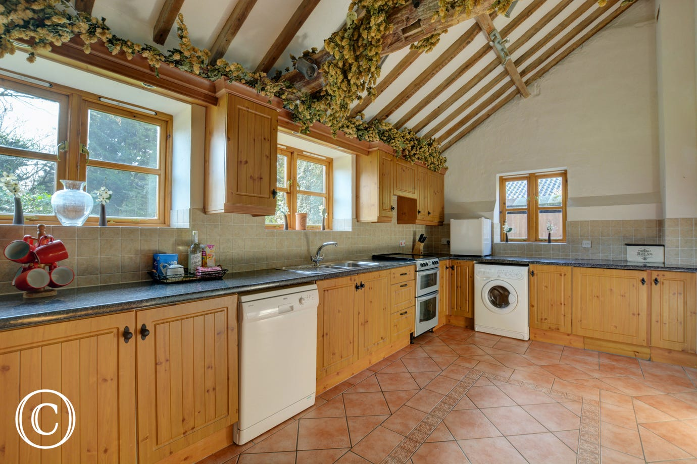 The kitchen is at the rear of the house, with a fitted electric cooker and washing machine. The exposed beams add character to the room