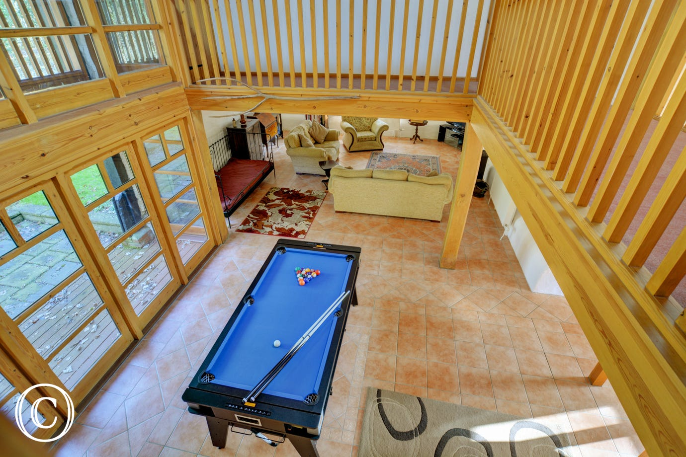 From the galleried landing you can look down to the pool table in the hall below