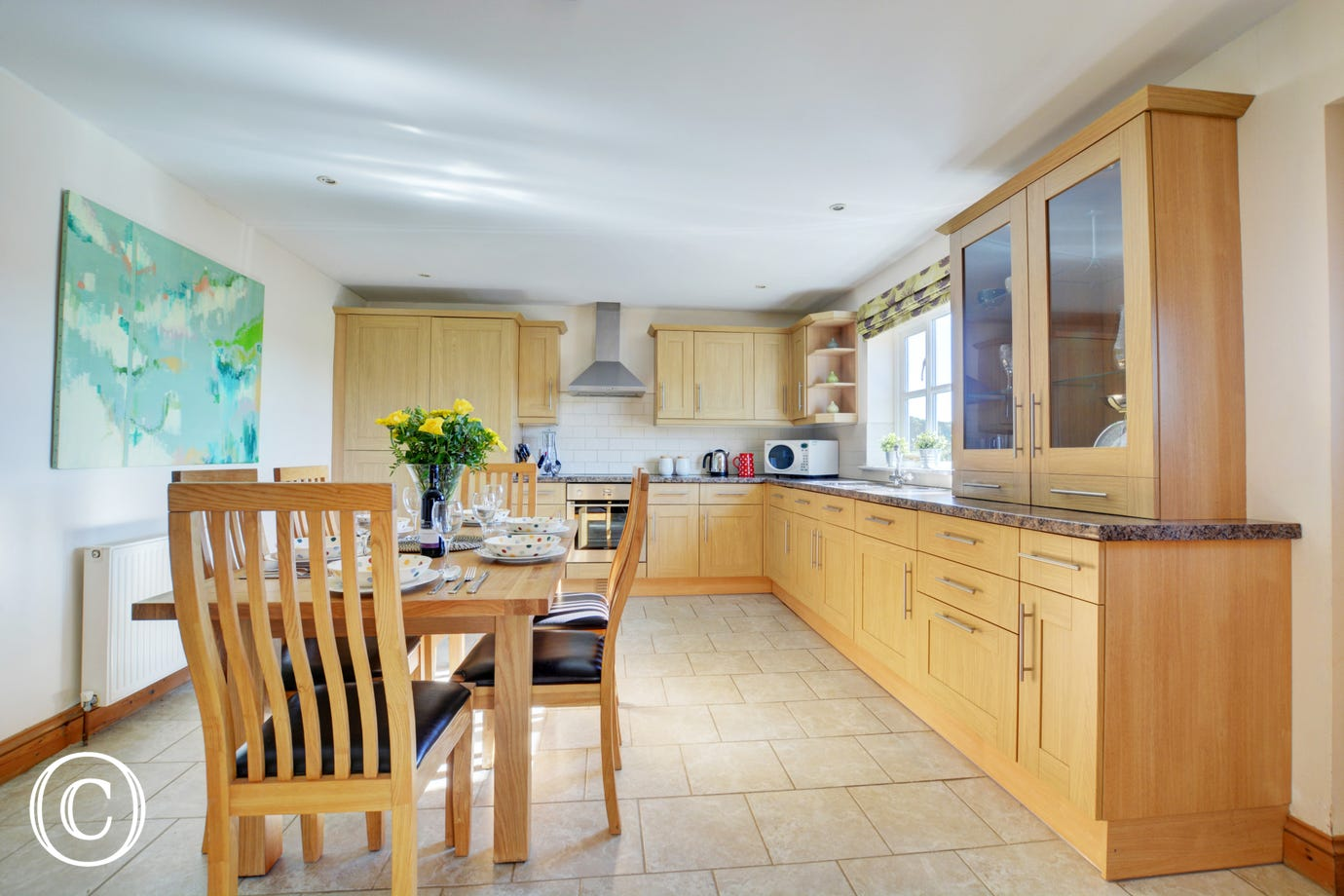 The kitchen is large and spacious with a table and chairs for dining, perfect for family meals