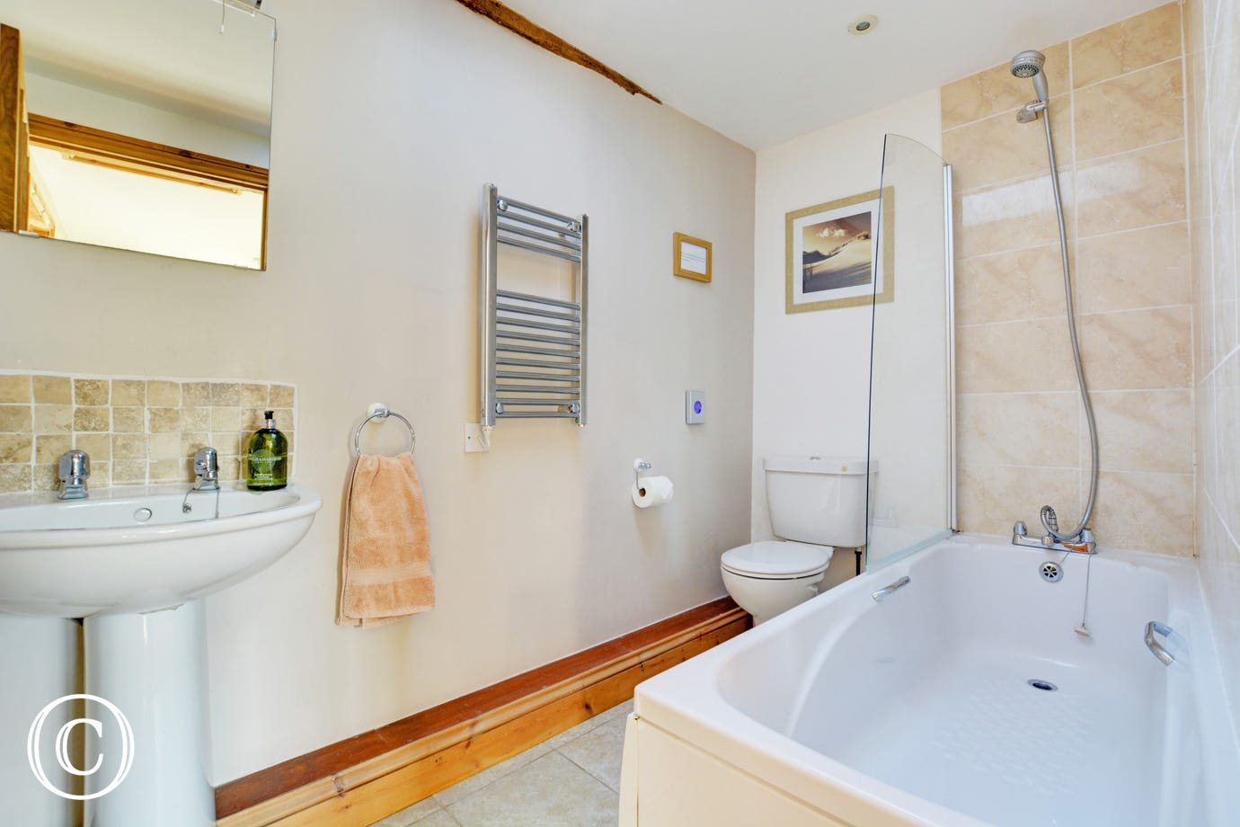 The modern bathroom has a bath and over bath shower, with lovely attention to detail