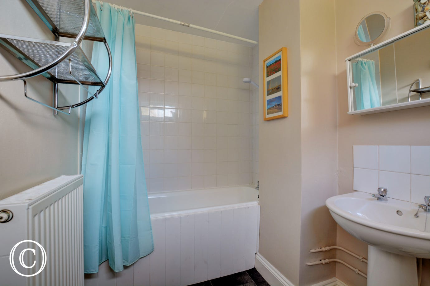 White bathroom suite with a bath and over bath shower