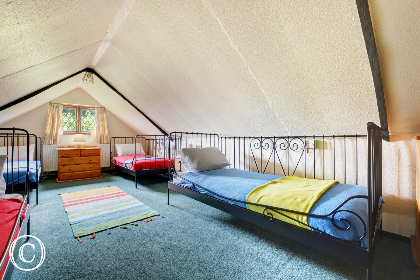 This bedroom has 4 single beds which makes an ideal childrens room