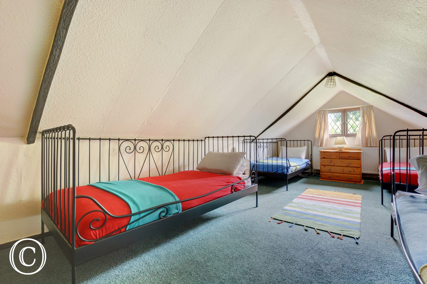The children's room has sloping ceilings and wrought iron bedsteads