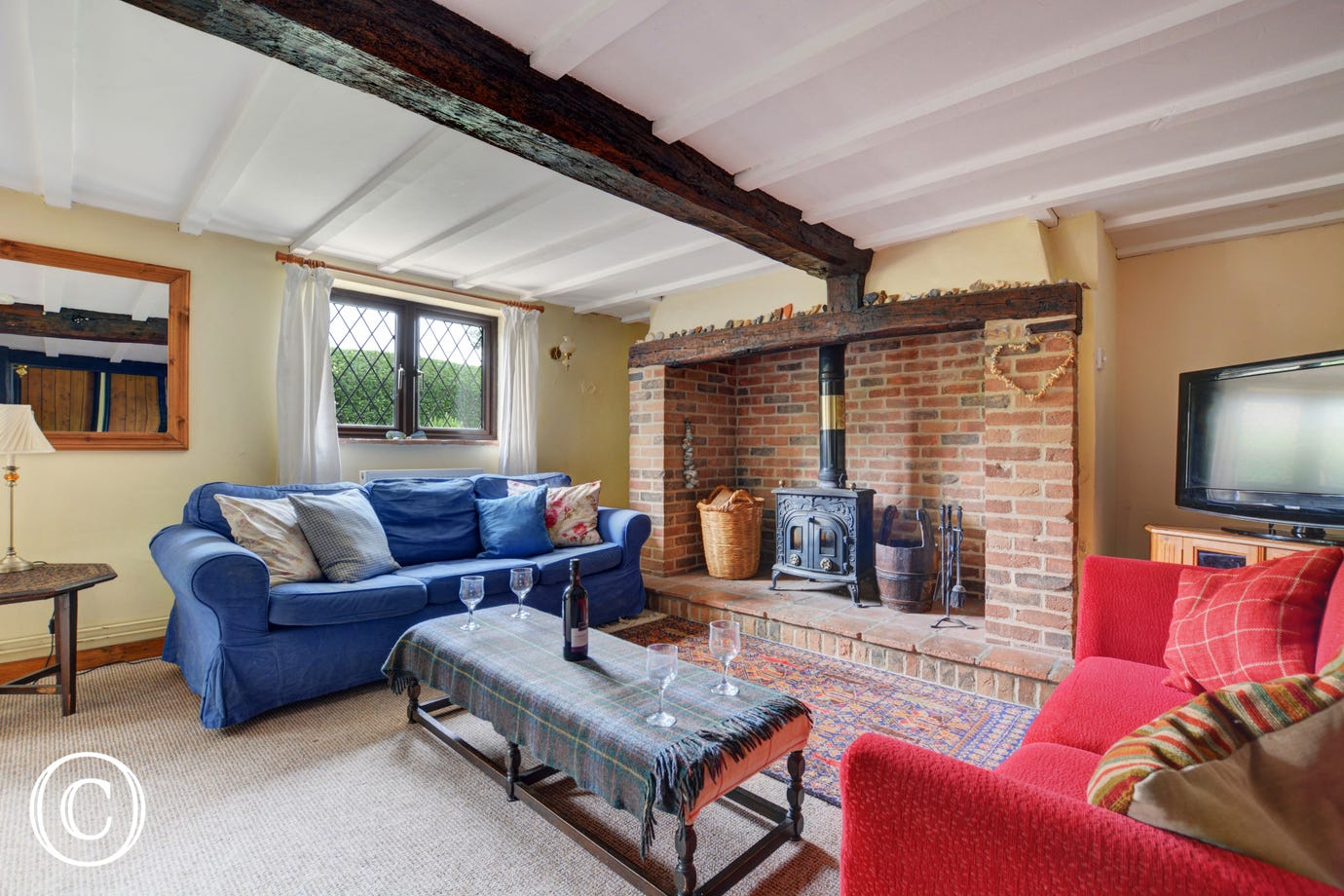 The lovely sitting room, with comfortable seating and a woodburner for cosy evenings