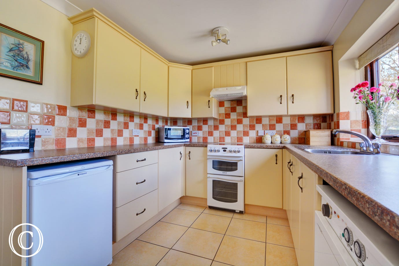 A spacious galley style kitchen cheerfully tiled.
