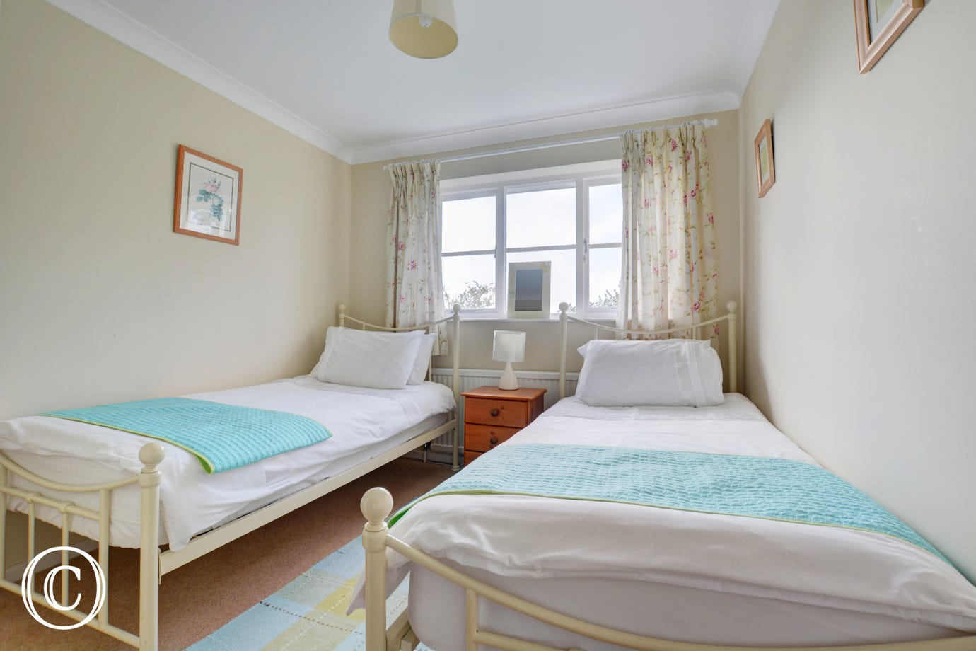 Bright double bedroom with wrought iron twin beds, ideal for children