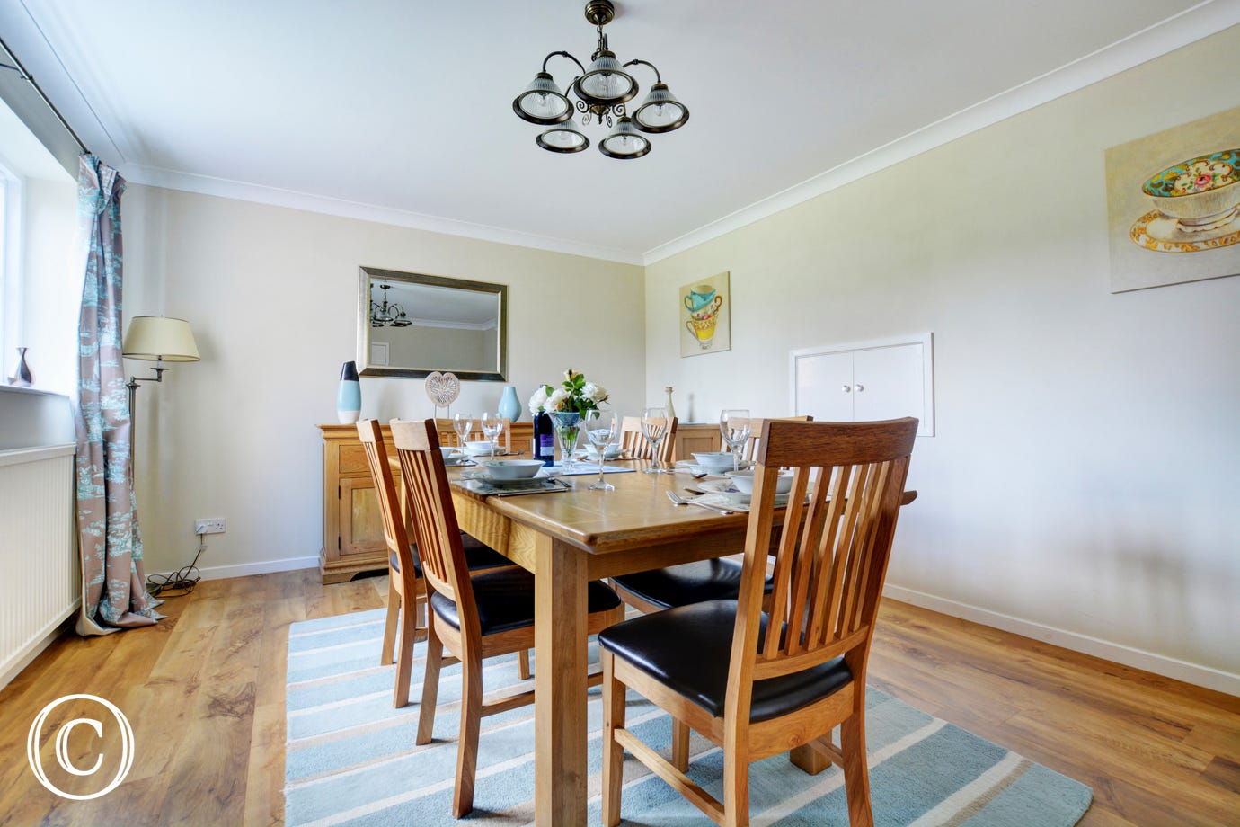 The charming dining room has a table and chairs, perfect for family meals