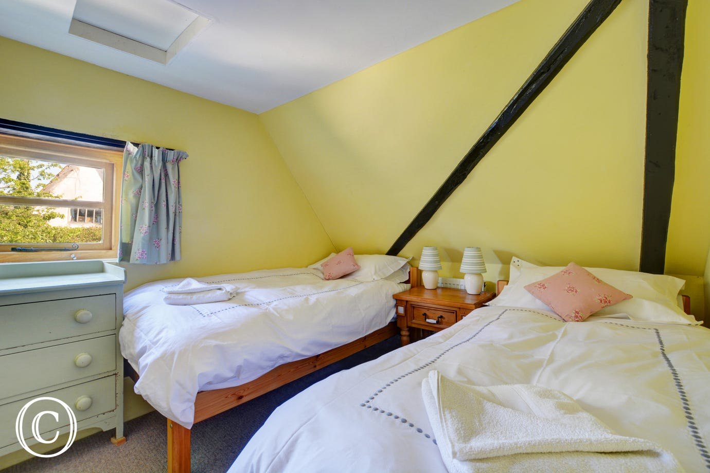 Cheerful double bedroom with twin beds, beams and a sloping ceiling