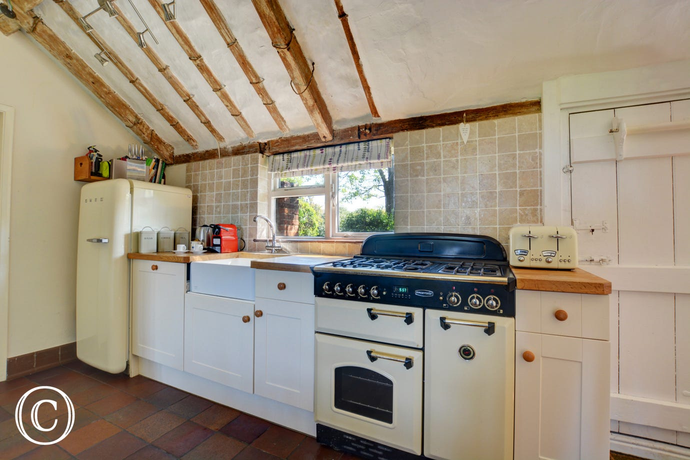 The Range cooker with a gas hob and electric oven is only one of the many appliances, with a butler sink and a small table and two high chairs, this kitchen is very well equipped and has an utility room