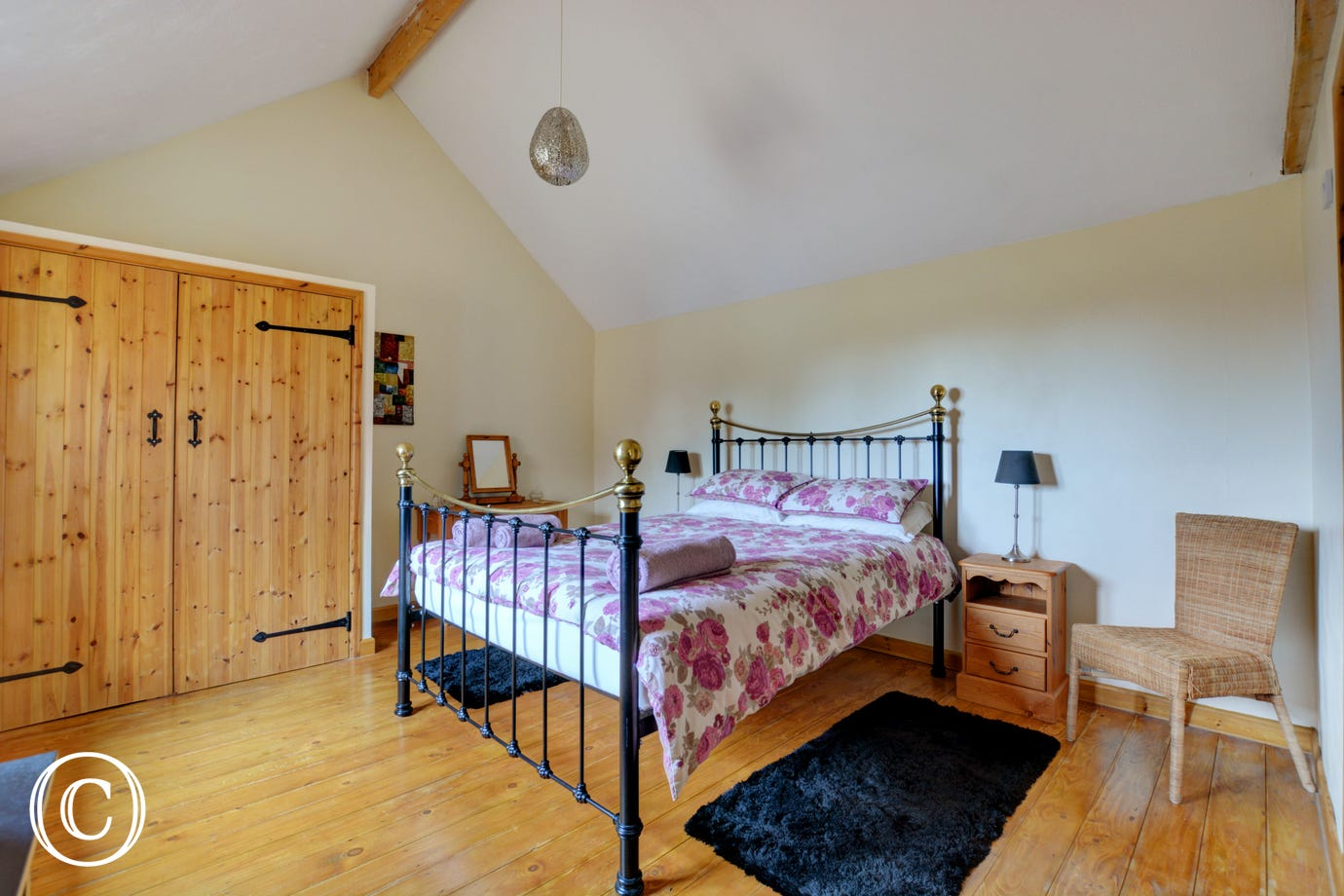 Double bedroom has plain linen with contrasting throw.  Plenty of storage in large pine wardrobe.  Wooden floors with rugs to the side of the bed for comfort.