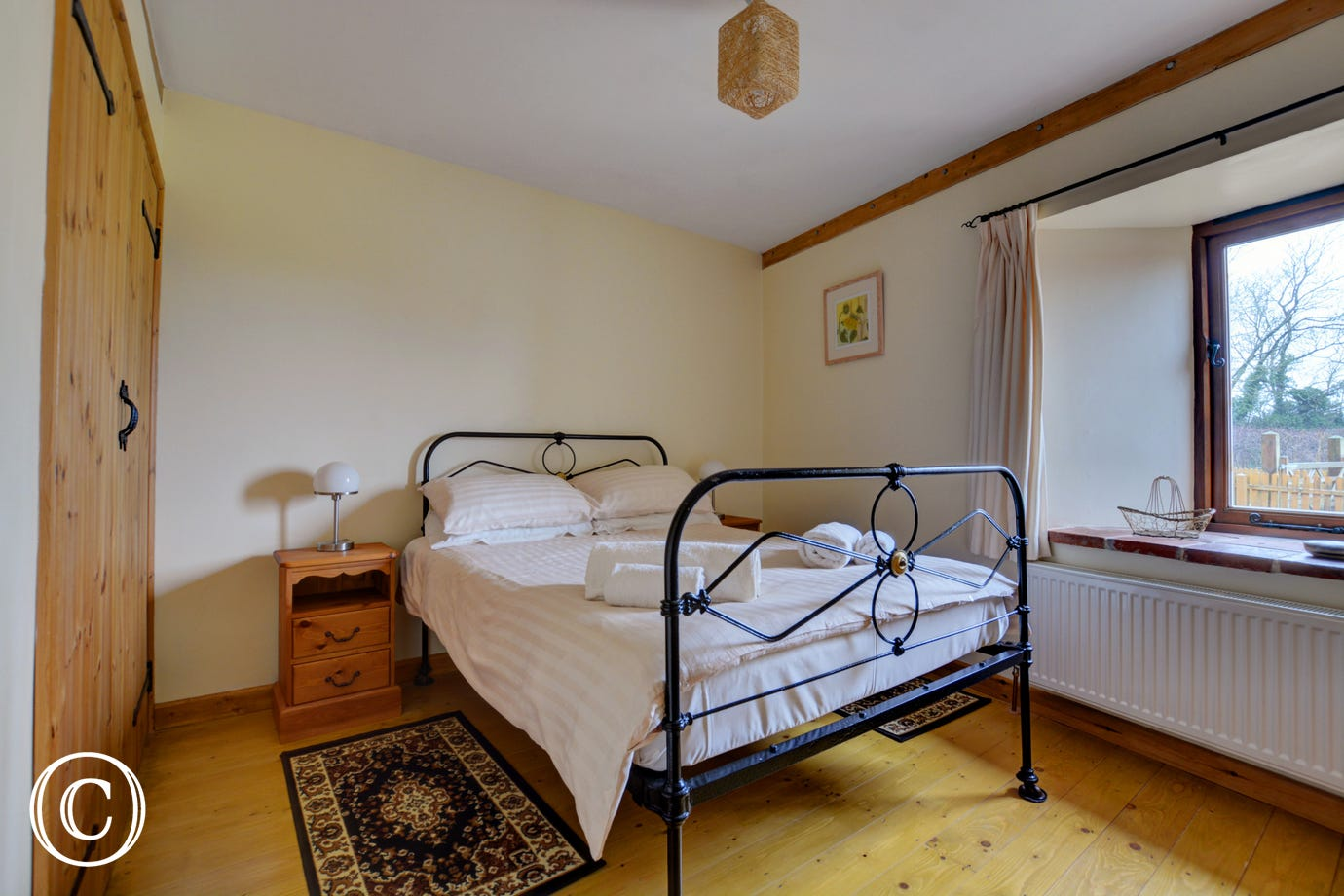 The second double bedroom with feature iron bed.  Wooden floors with cosy rugs beside the bed