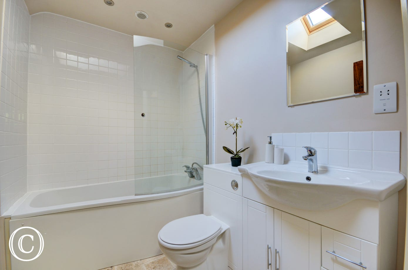 The ensuite off of bedroom one has a curved bath with an over bath shower, washbasin and wc