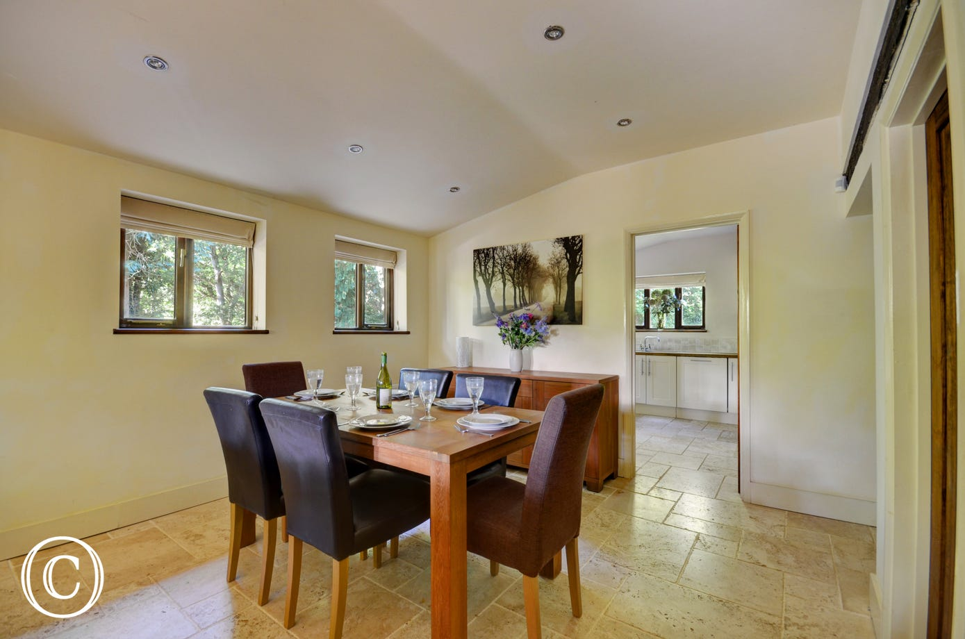 The dining room has an attractive dining table with six chairs and leads through to the kitchen