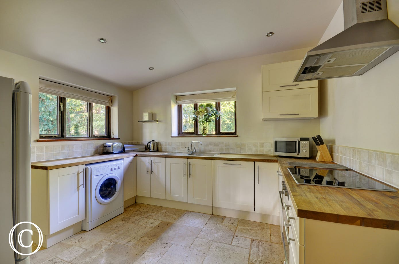 The built in cooker has a stainless steel cooker hood with extractor over, the window looks out to the garden