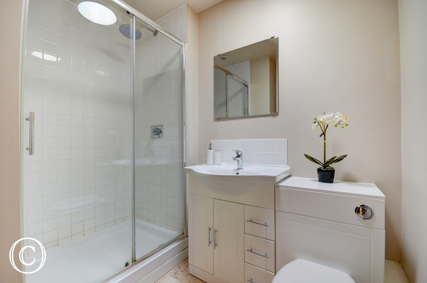 The fully tiled shower room has a large shower enclosure with a sliding glass door