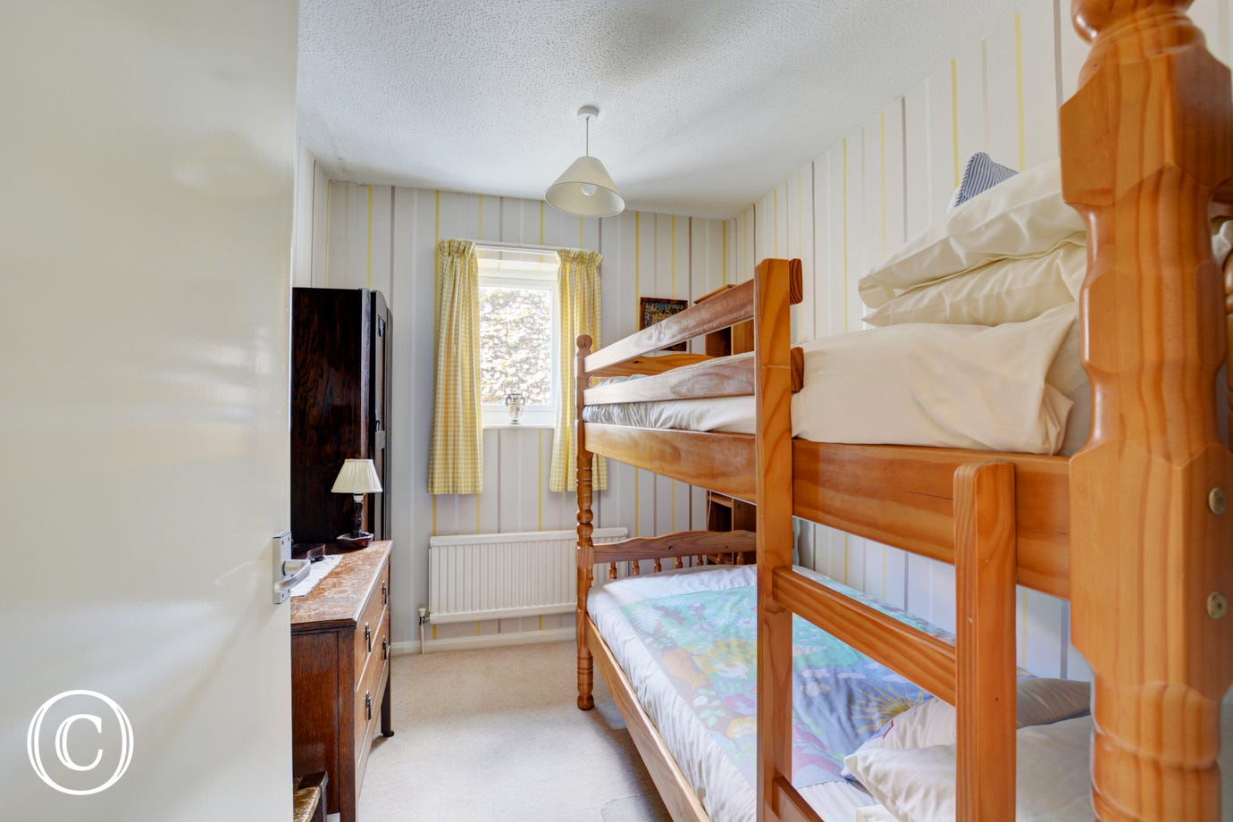 Cottage style bedroom with wooden bunk beds, perfect for children