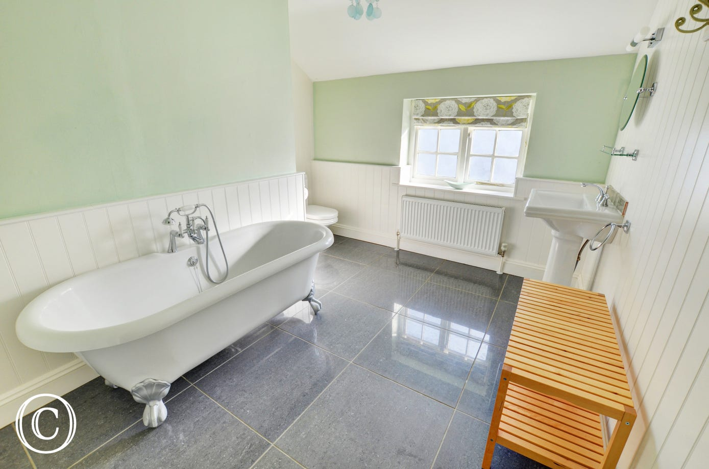 Spacious bathroom with stunning roll top bath