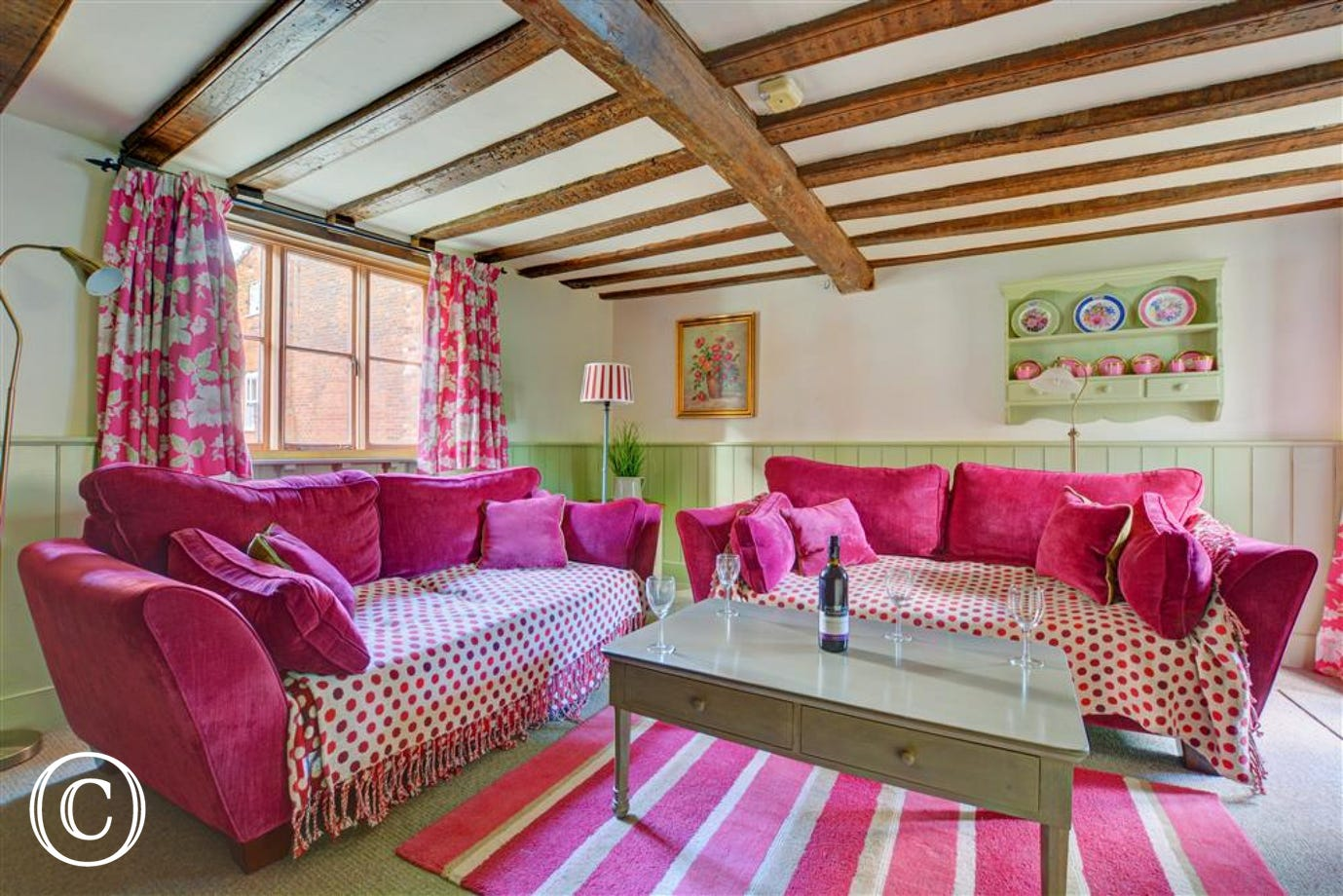 Lovely cottage living room, with a pretty colour scheme of natural, green and raspbery soft furnishings and comfortable seating.