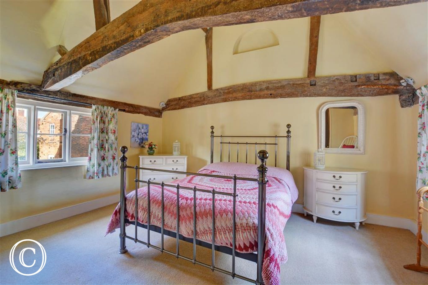 Bright, pretty and spacious bedroom with exposed beams.