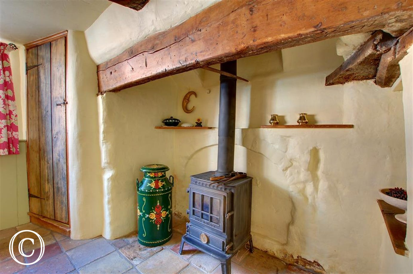 The little wood burner set in the large open fireplace of the dining room.