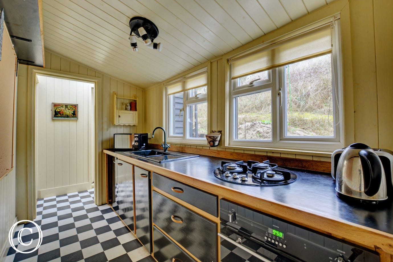 A compact stylish kitchen with gas hob and electric over with views over the sand dunes.