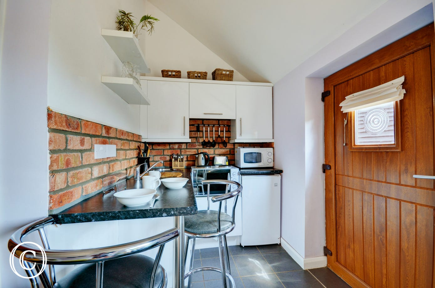 The compact kitchen area has an electric mini fan-assisted oven and two rings, full-size fridge with icebox, microwave and breakfast bar with two bar stools