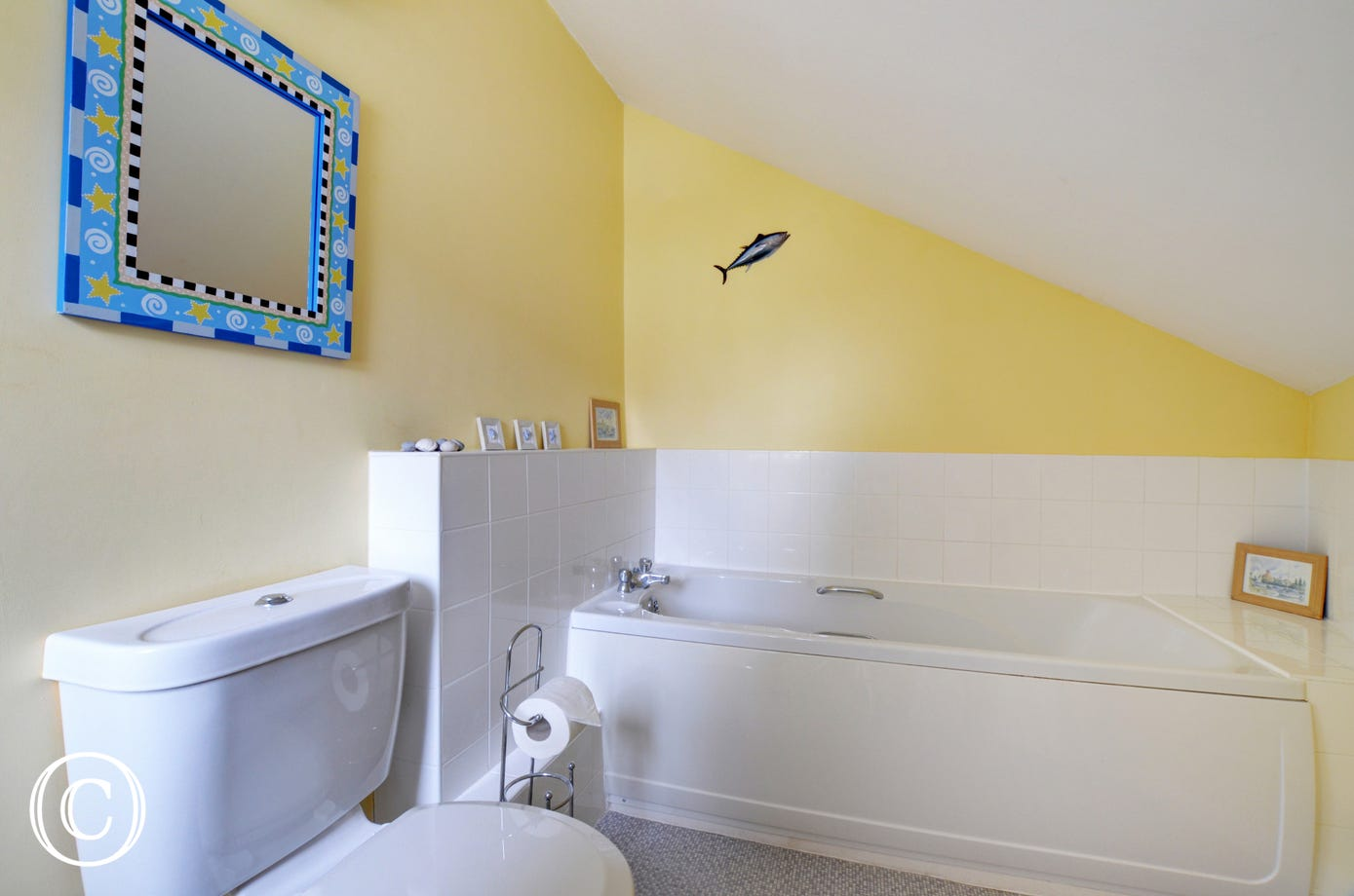 A bathroom with white suite and brightly coloured walls.