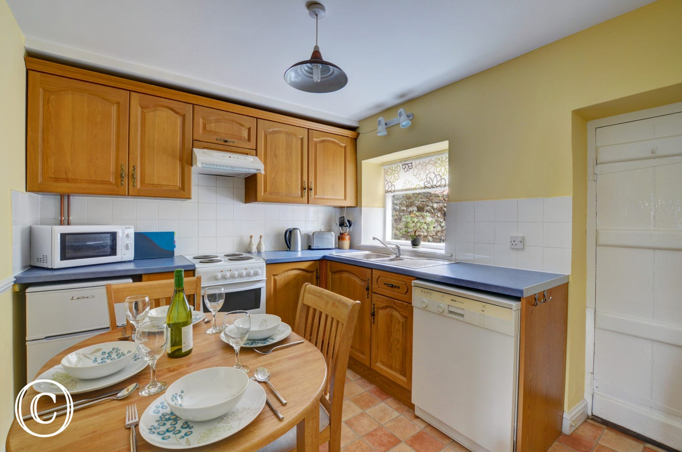 There is an electric hob and oven, fridge with icebox, microwave, dishwasher and table and chairs in for kitchen dining.