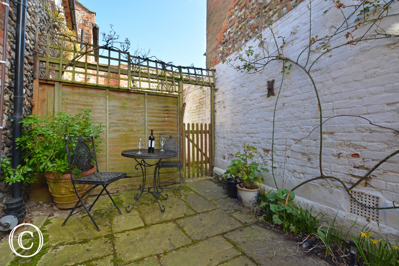 Small paved courtyard with small table and 2 chairs,