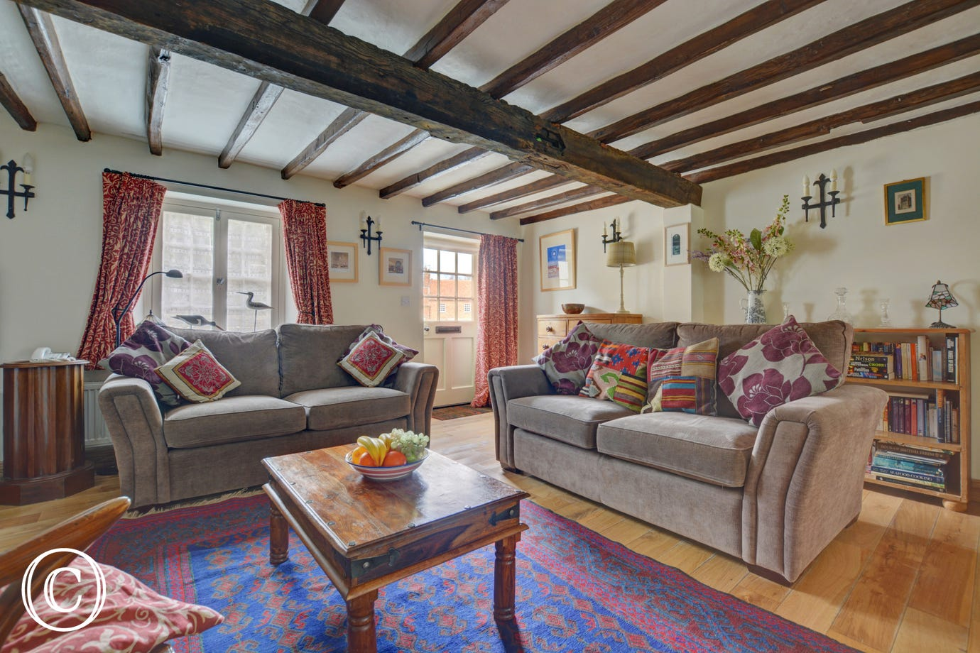 Cosy cottage sitting room, with beams. Decor in warm shades of cream reds and browns and furnished with 2 comfy sofas.