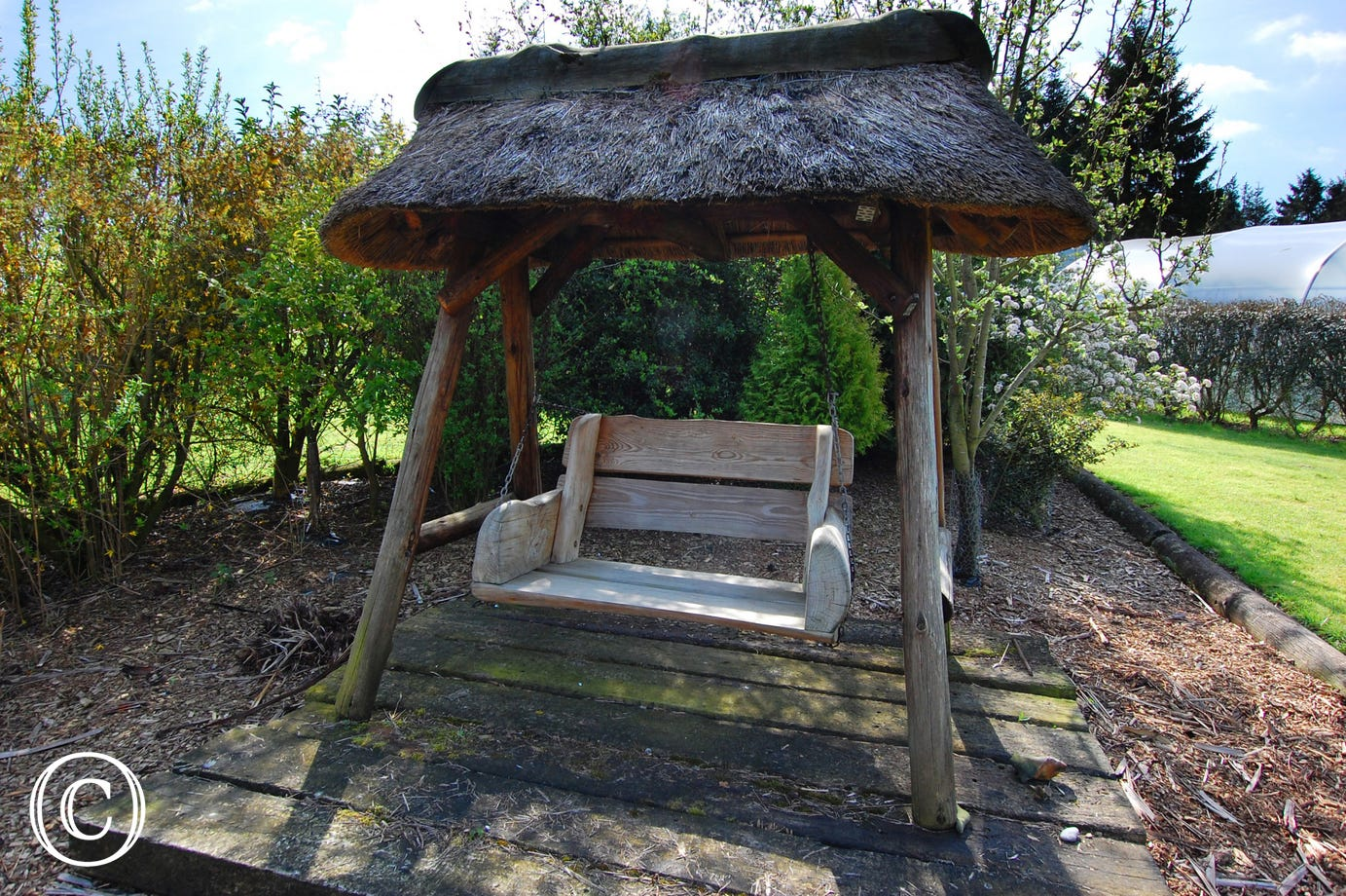 A thatch roof swing seat beside the pond