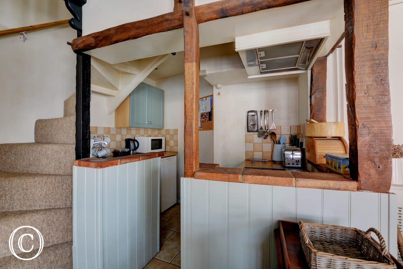 Compact kitchen with appliances situated at the bottom of the cottage style stairs.