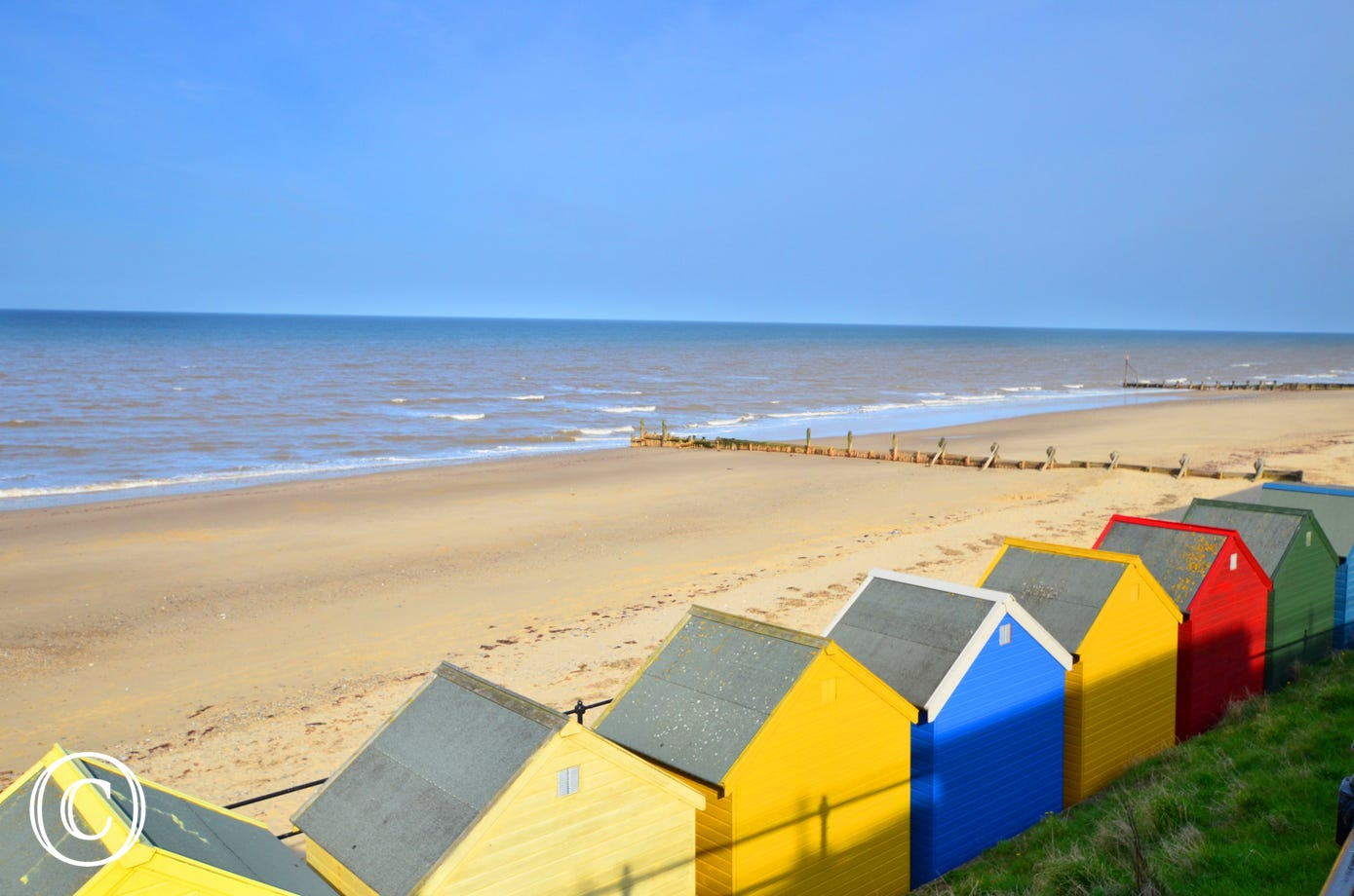 Multi-coloured beach huts adorn the sea front.