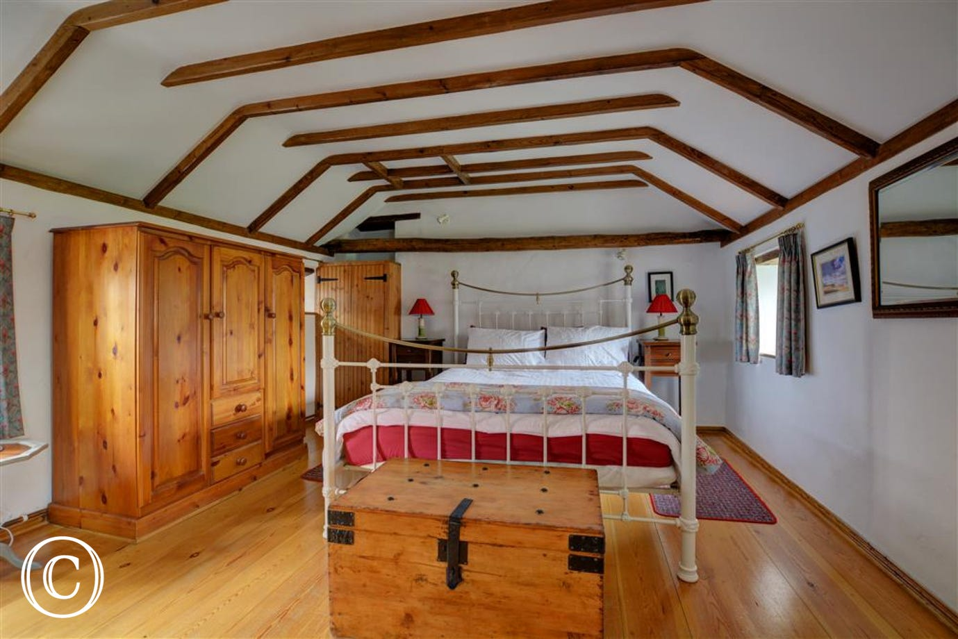 View of the bedroom with kingsize wrought iron bed, pine furniture and beams a room with true cottage style.