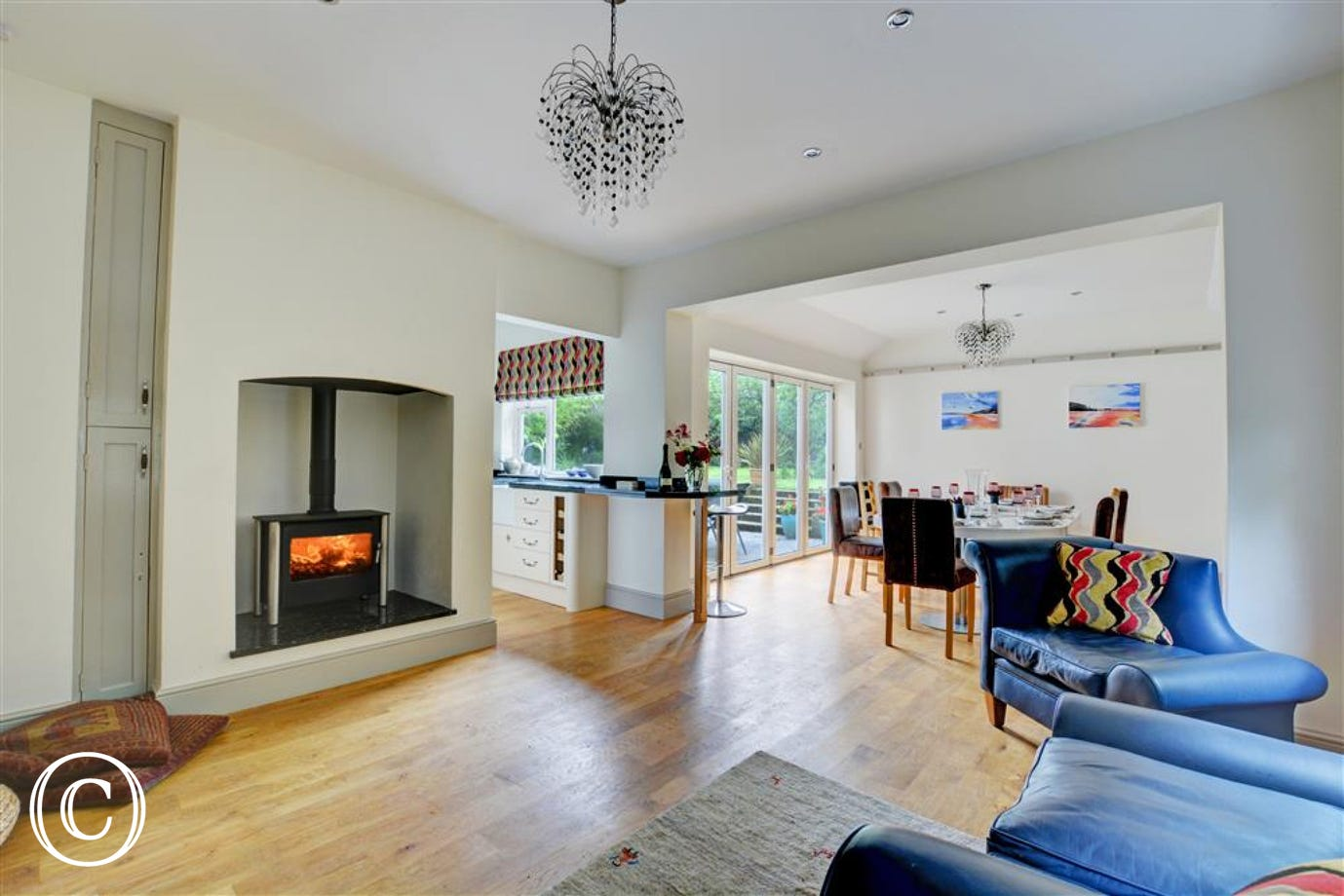 The open plan living room has a gas living flame fire