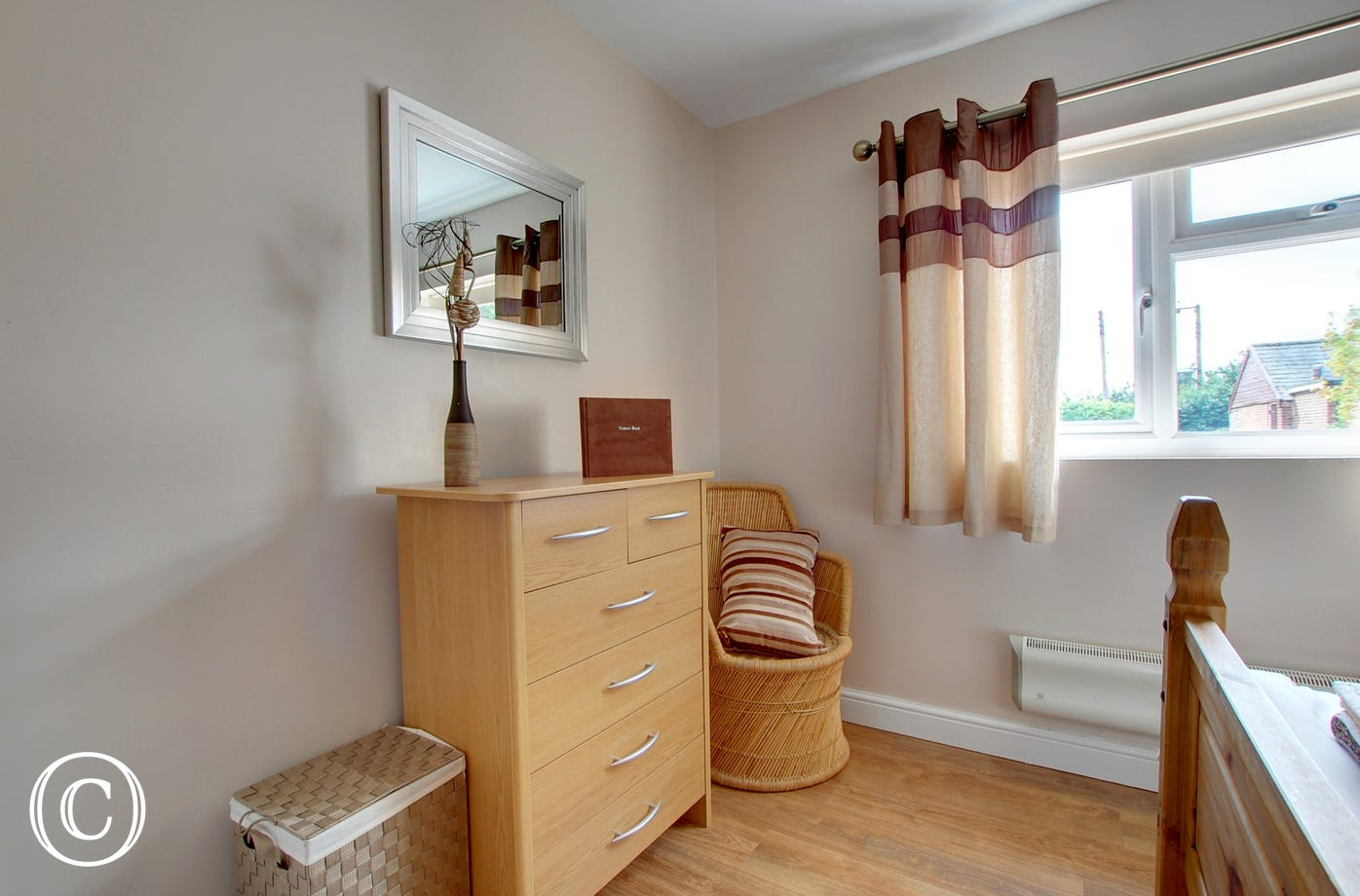 Tall chest of drawers with mirror above, wicker chair positioned in corner of room.