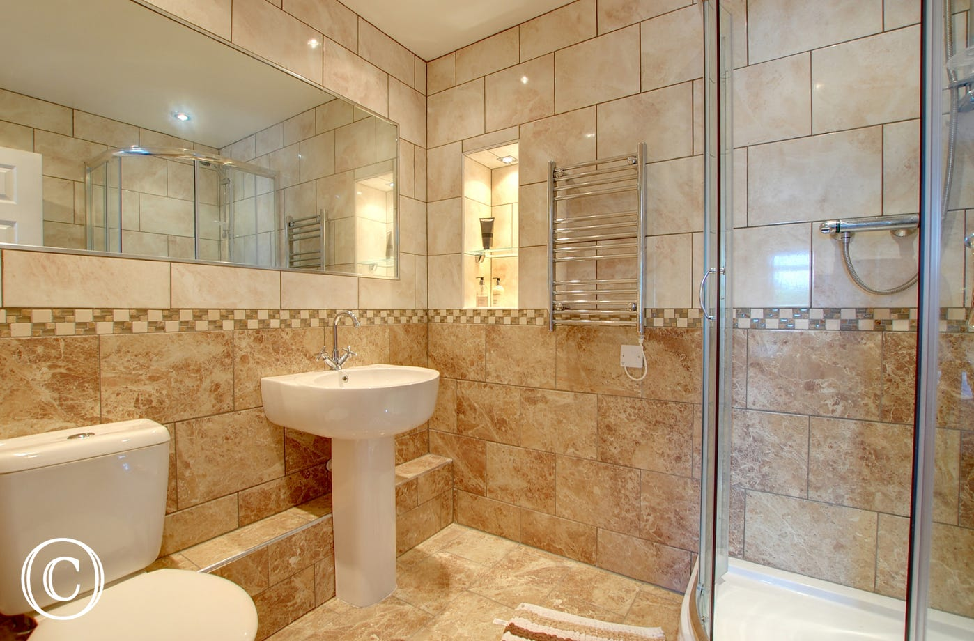 Fully tiled shower room, heated towel rail.
