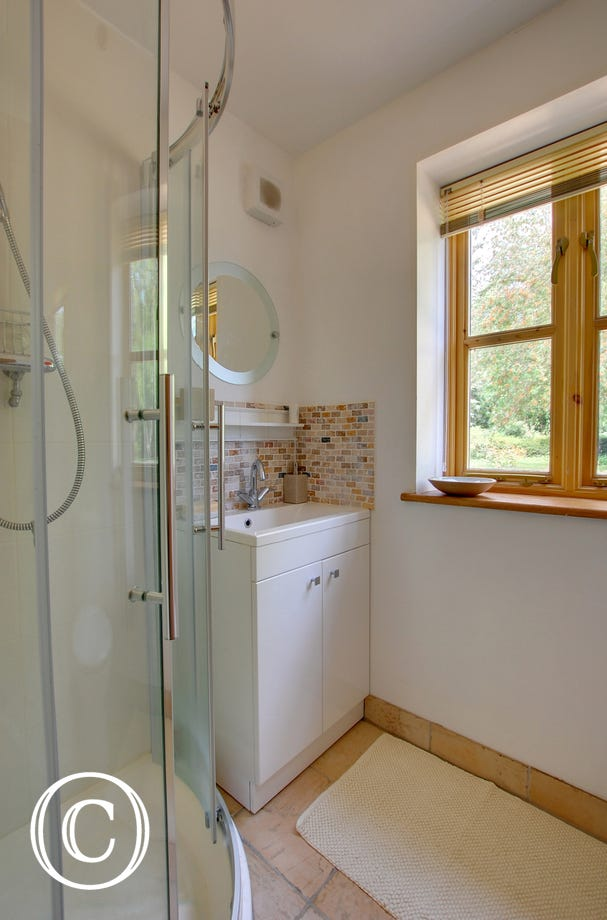Shower room with shower cubicle, vanity unit and pretty mosaic tiles.