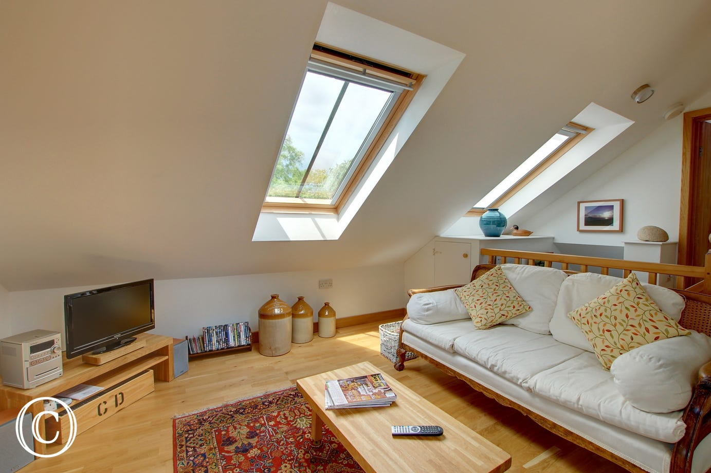 Bright and airy sitting room with 2 velux windows allowing light in.