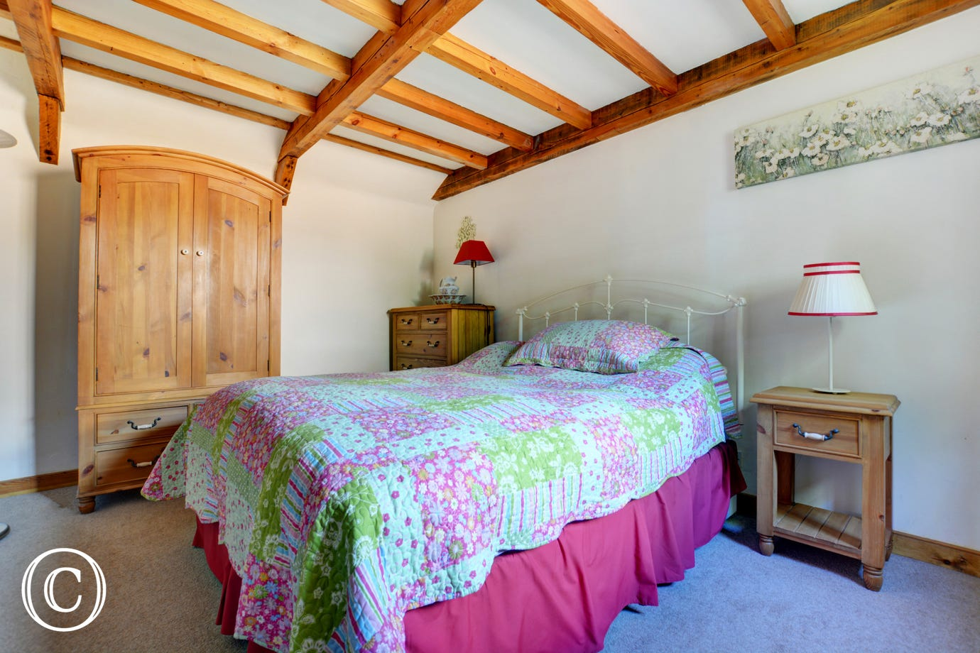 Very pretty country styled bedroom wtih beams, pine furniture, wrought iron bed and floral bedlinen in blues and pink.
