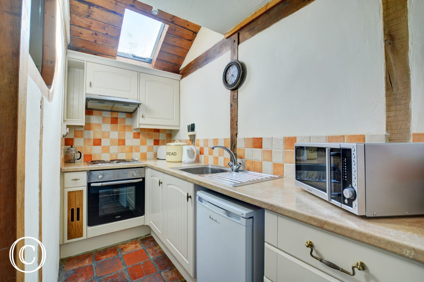 Compact and well presented kitchen with velux window, shades of cream beige and terracotta floor tiles.