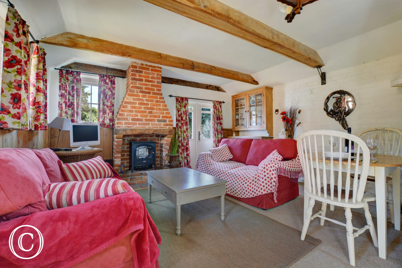 Cosy country cottage style living room, with beams and wood burner stove.