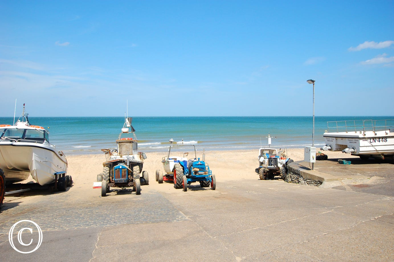Boats and tractors lined up on the beach.